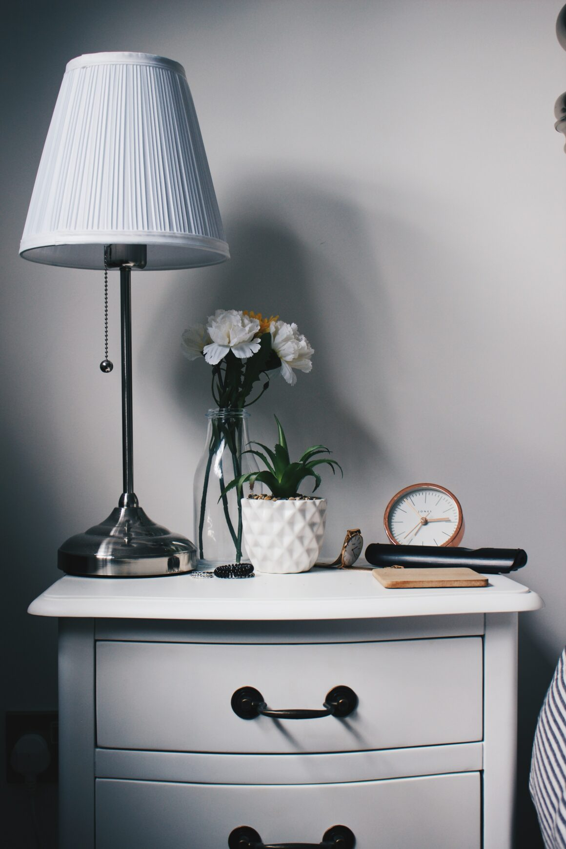 White bedside table decorated with a lamp, flowers, alarm clock, and remote