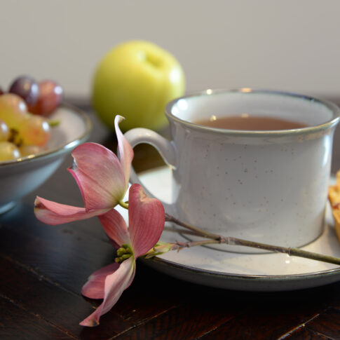 coffee grapes and flowers on a dark table