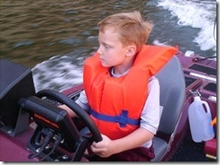 My son learning to operate a boat.