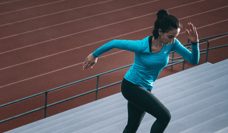 female personal trainer running on stairs for small changes to create big results with HIIT training