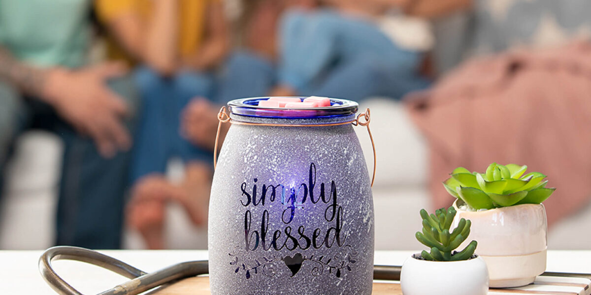 Scentsy 'Simply Blessed' Warmer in a lifestyle shot next to little succulents, people in the background talking