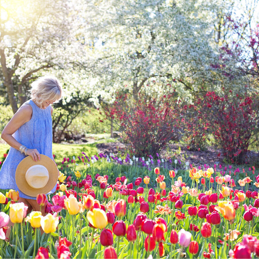 Woman walking through flower field holding onto her hat