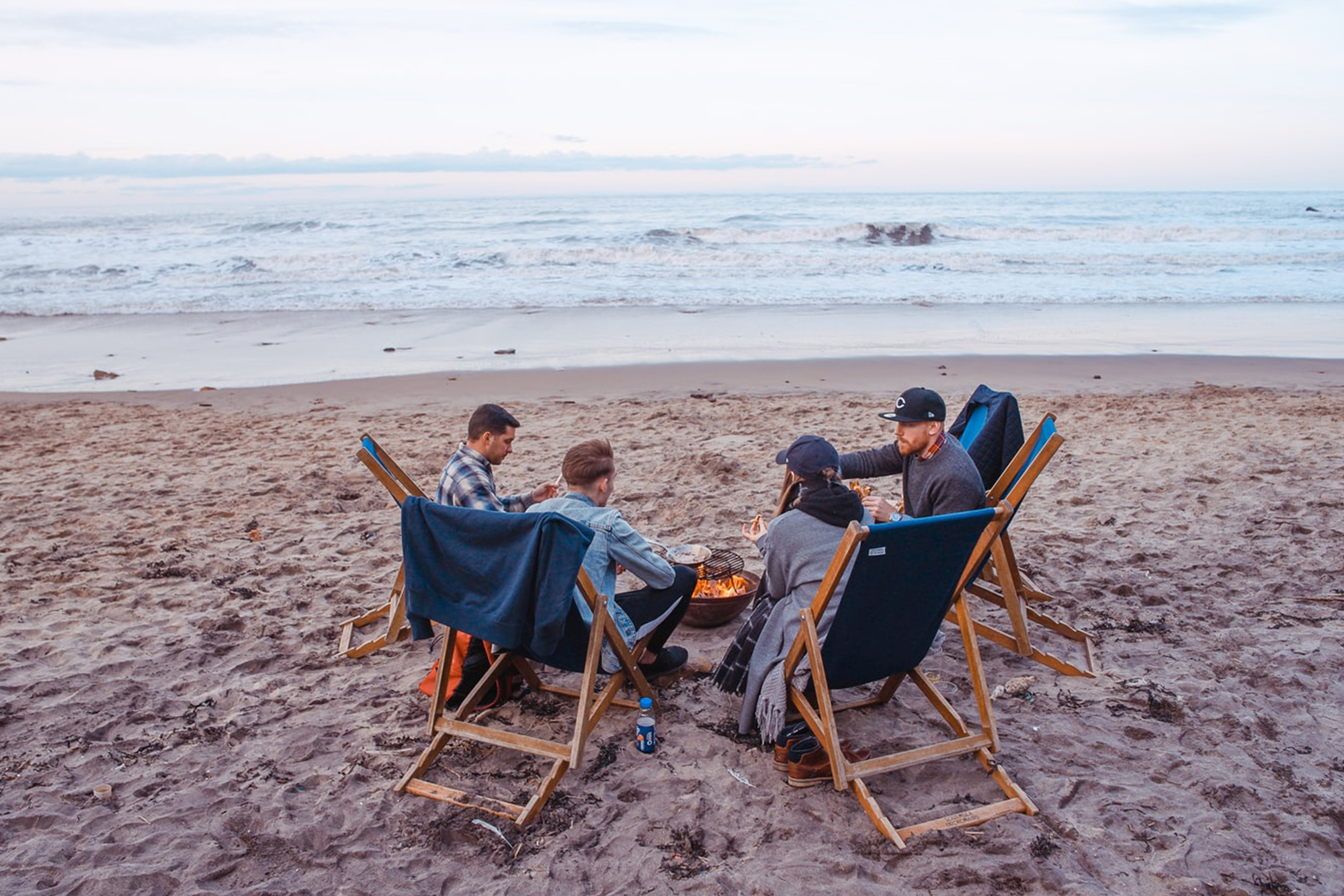 Friends sitting around a beach bonfire
