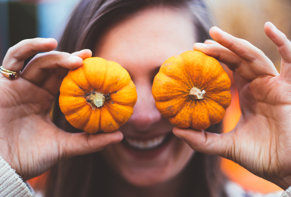 photo of woman holding pumpkins over her face