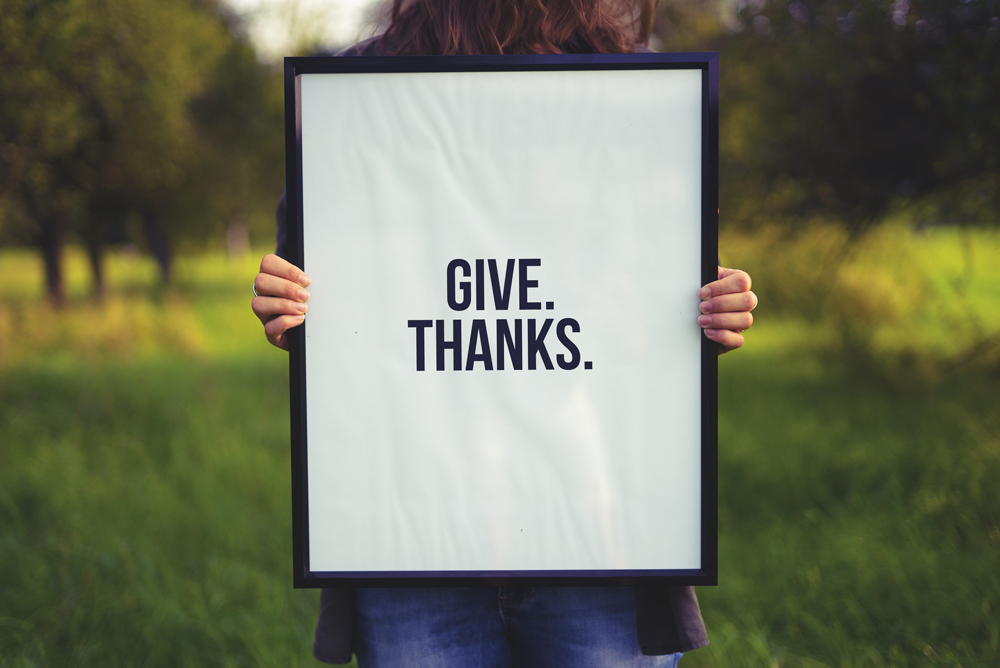 Photo of woman holding frame prompting to give thanks