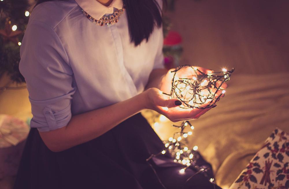 woman holding christmas lights