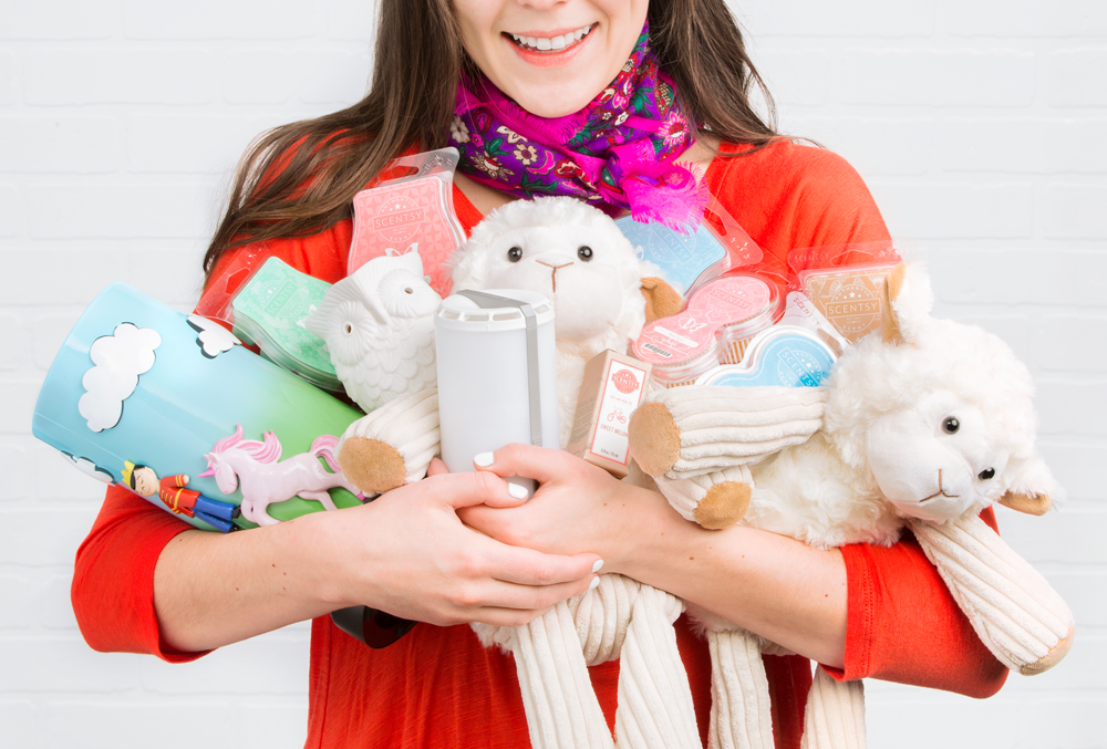 Photo of woman holding a ton of Scentsy products