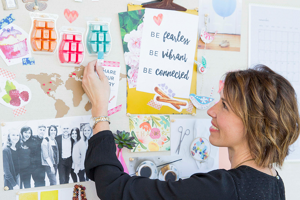 Photo of CEO Heidi matching a pantone in front of a Scentsy mood board