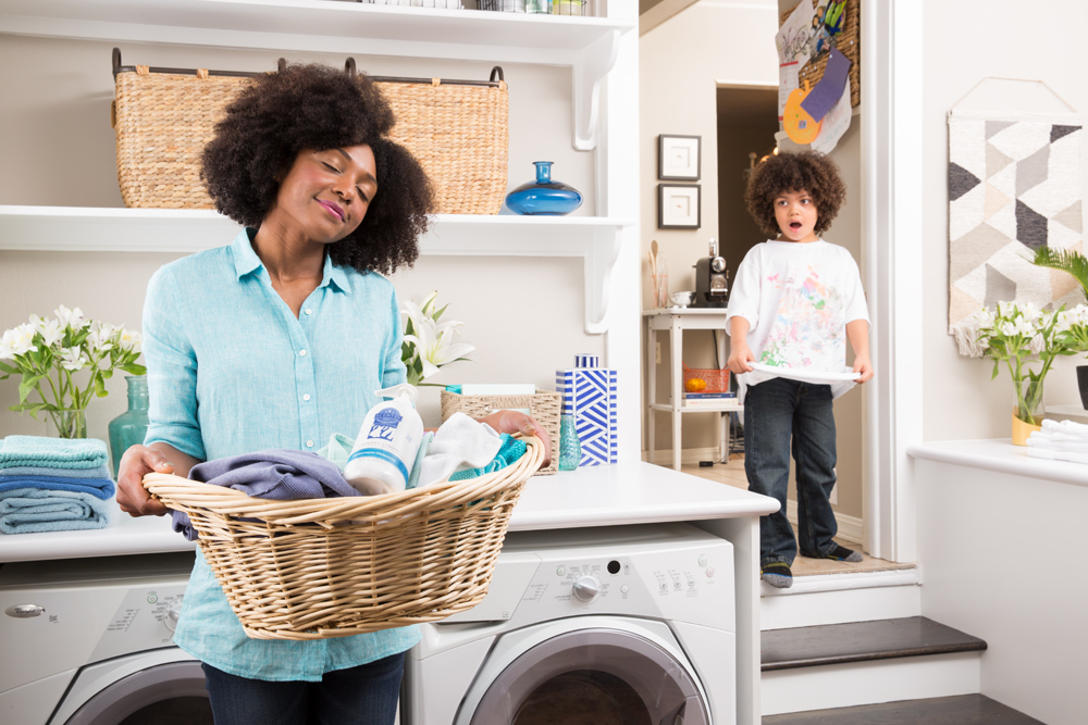 Photo of mom holding basket of clean laundry with her looks toward her in the background