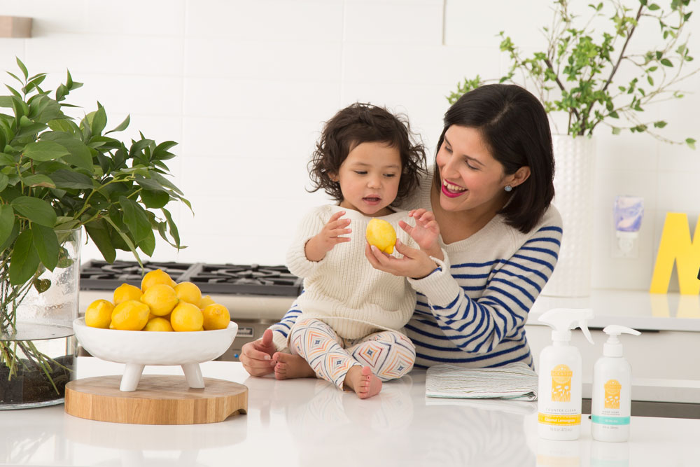 Mother holding child in Kitchen next to Scentsy Clean products