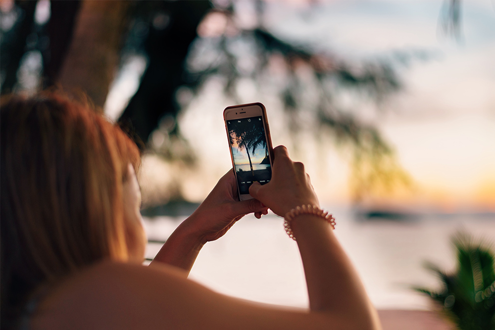 Photo of woman taking a photo of a beach with her phone camera