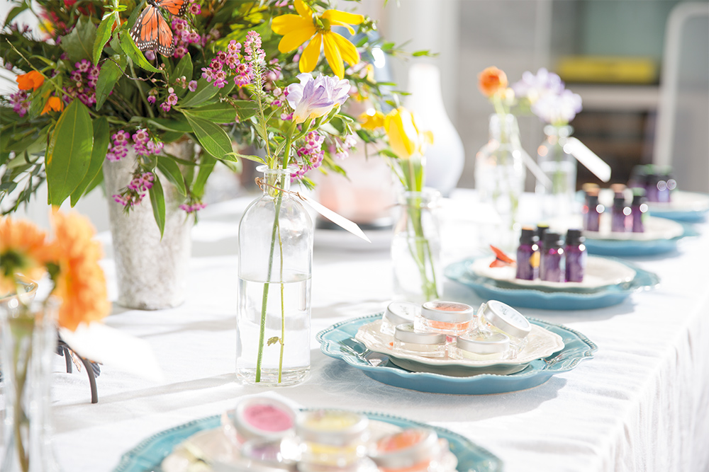 Photo of fresh flowers on a garden table with Scentsy testers and essential oils