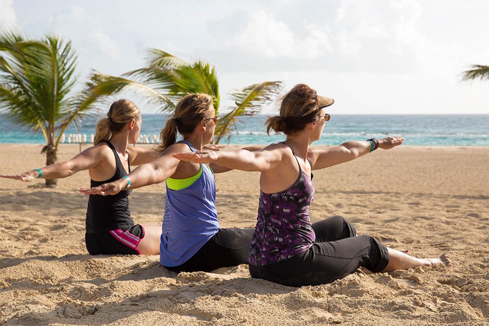 Photo of women doing yoga on the scenic beach