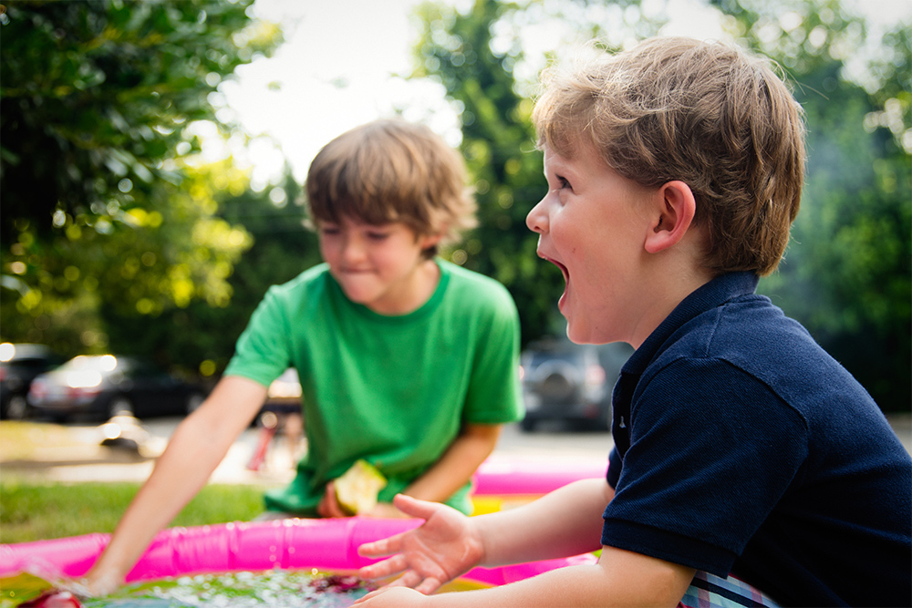 Photo of kids playing laughing in mini pool