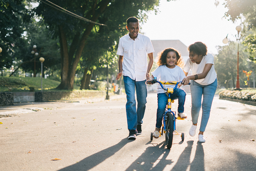 photo of parents teaching their daughter to bike