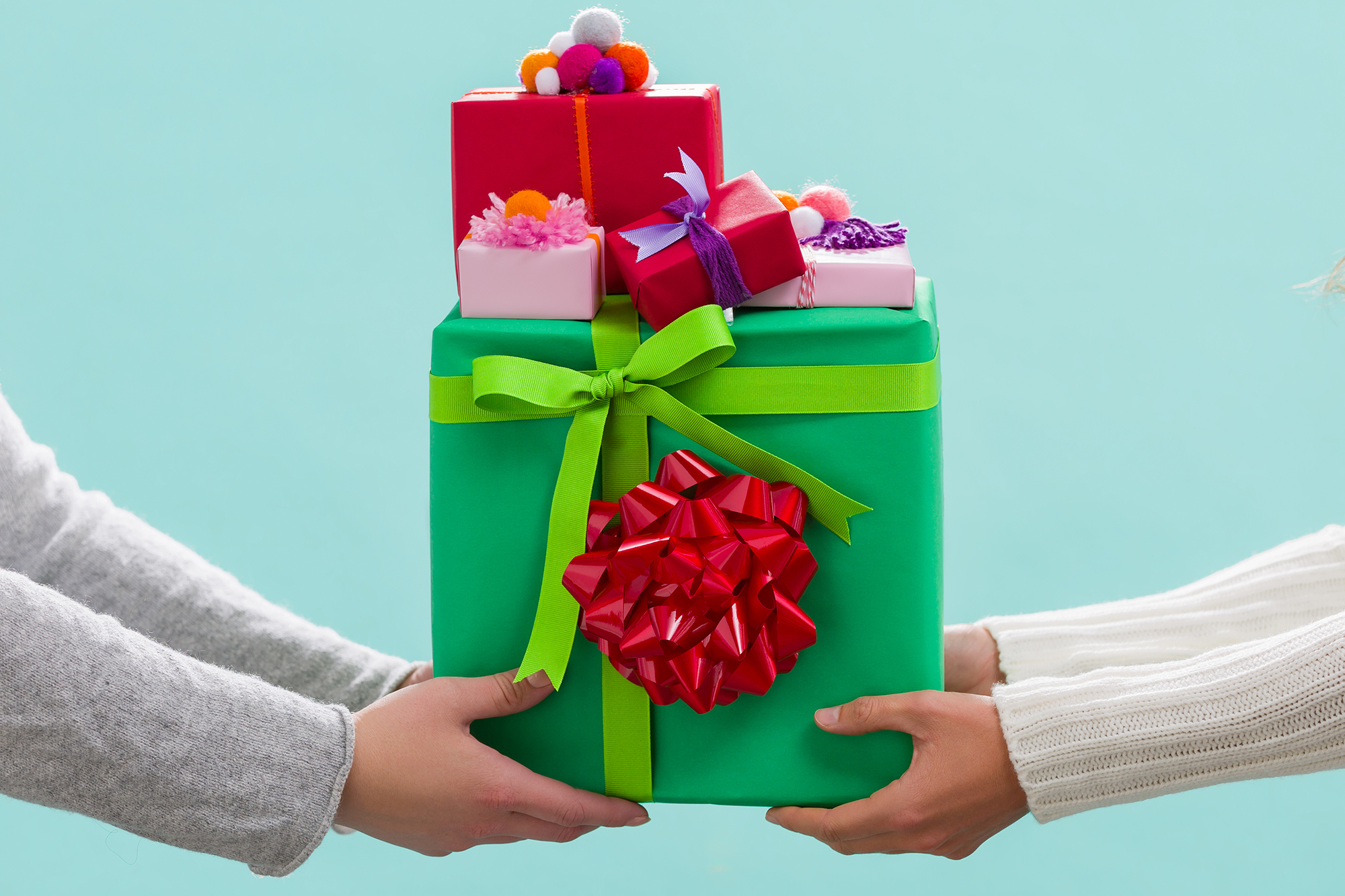 Photo of two women exchanging pile of gifts