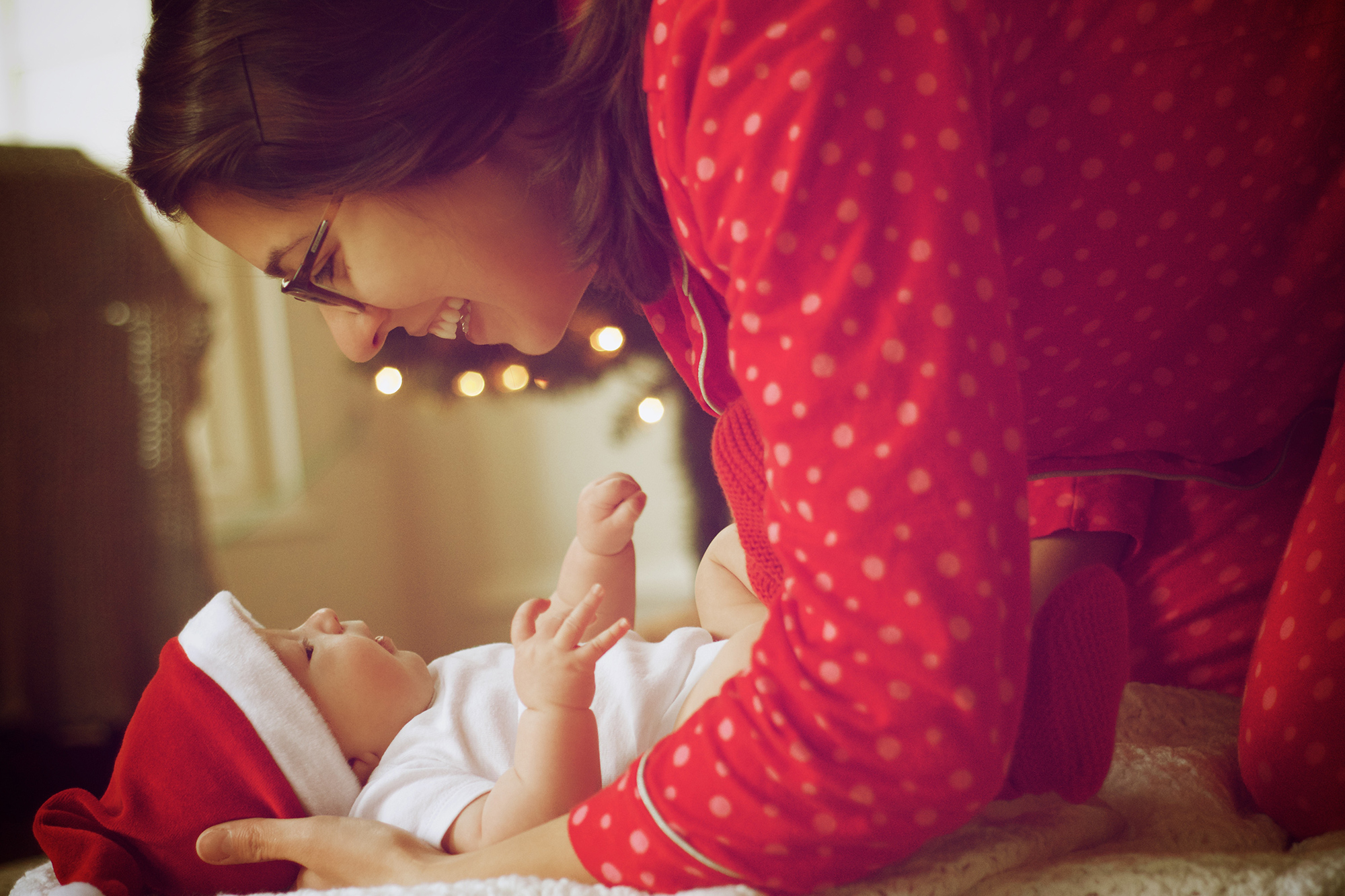 Photo of mother smiling at her baby in front of Christmas tree