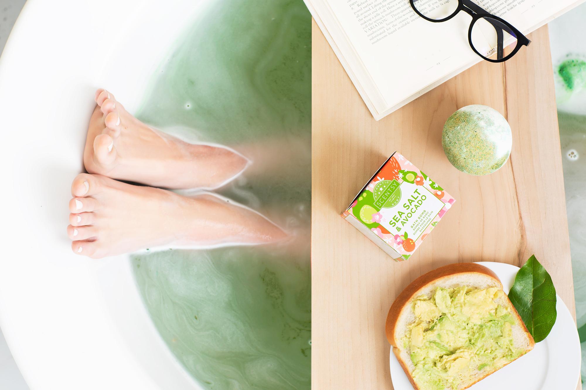 Photo of woman's feet soaking in a Scenty sea salt and avocado bath bomb bath