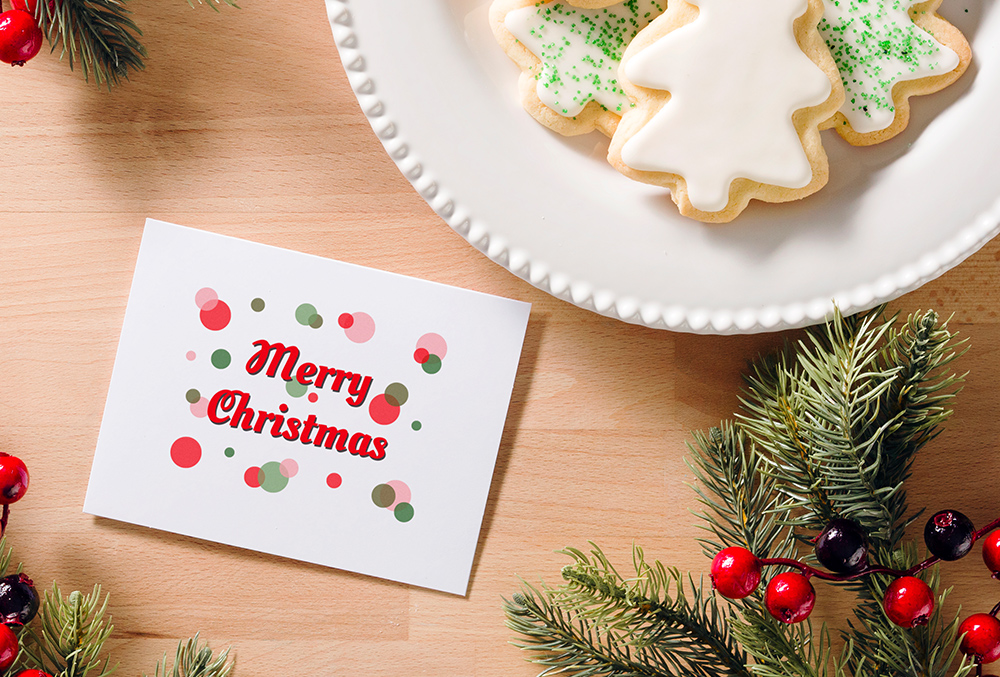 Photo of merry christmas card aside a plate of cookies