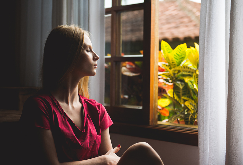 photo of woman breathing deeply aside an open window