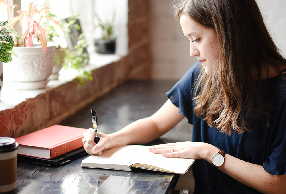 Photo of woman writing in planner