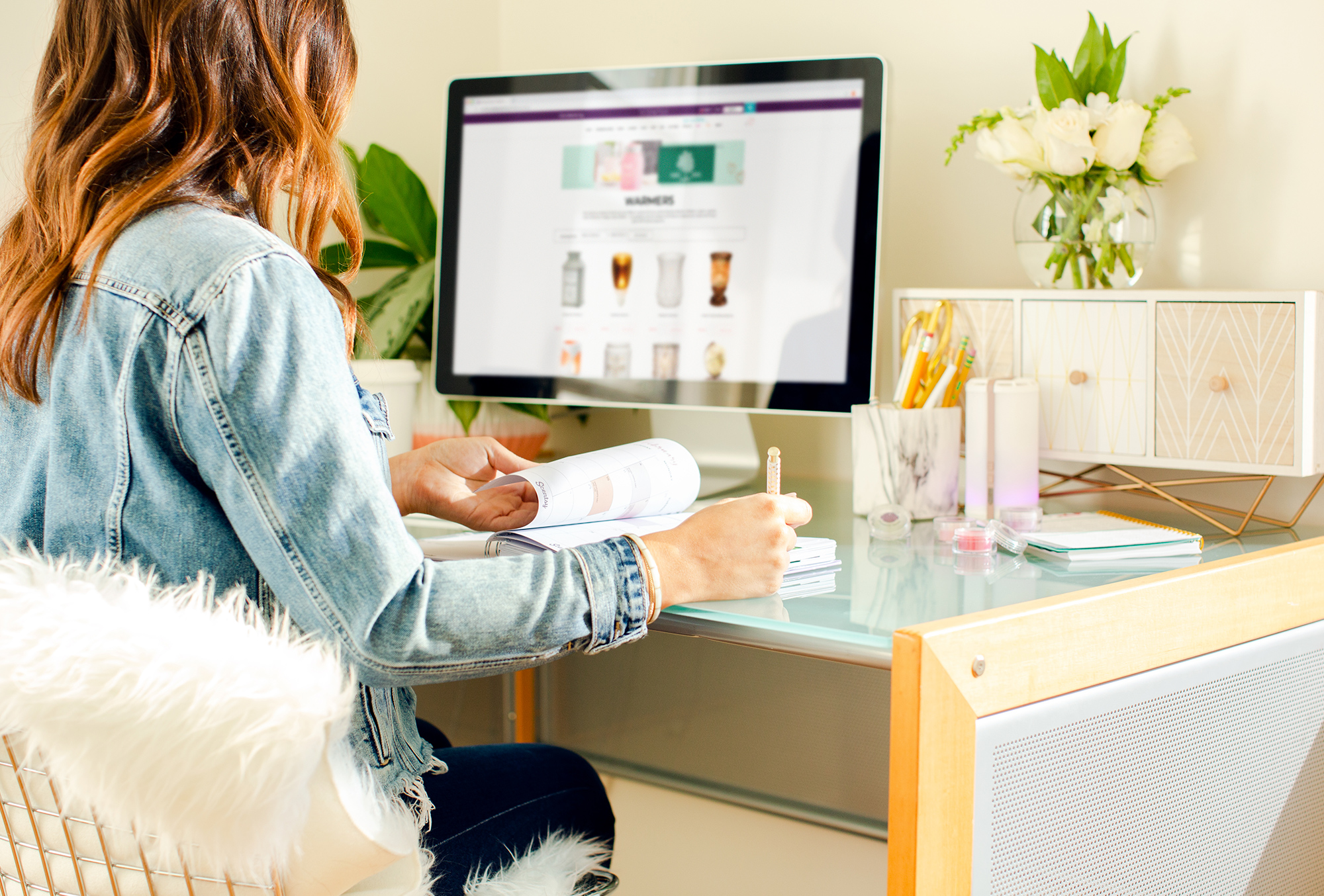 Consultant taking notes while looking at Scentsy product on Scentsys website