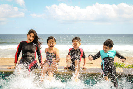 Mother and her children laughing on a surf board in the ocean waves