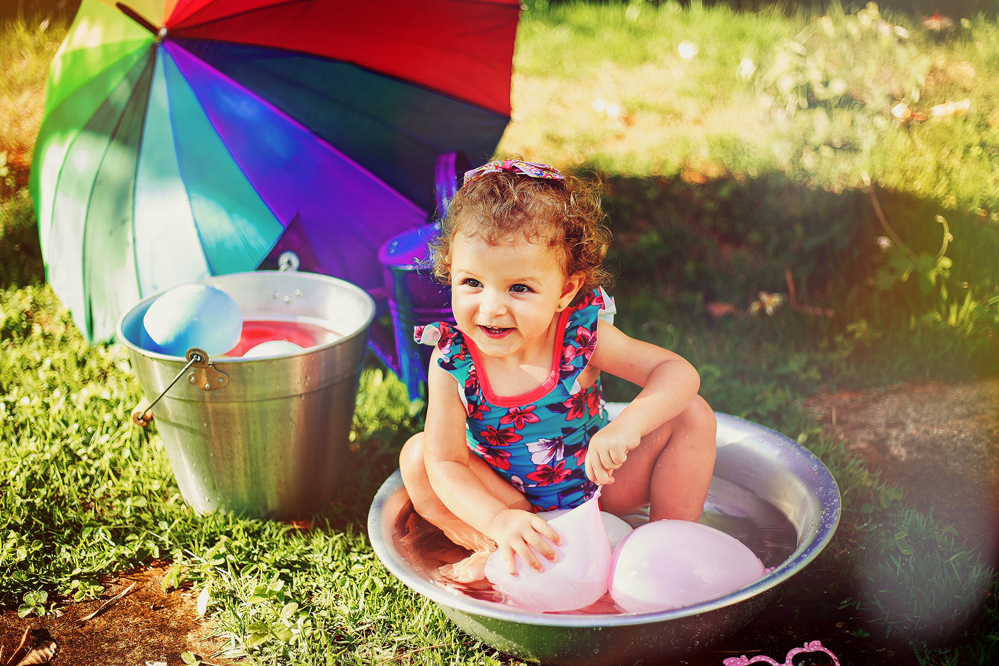 Little girl laughing playing in bucket with water ballons
