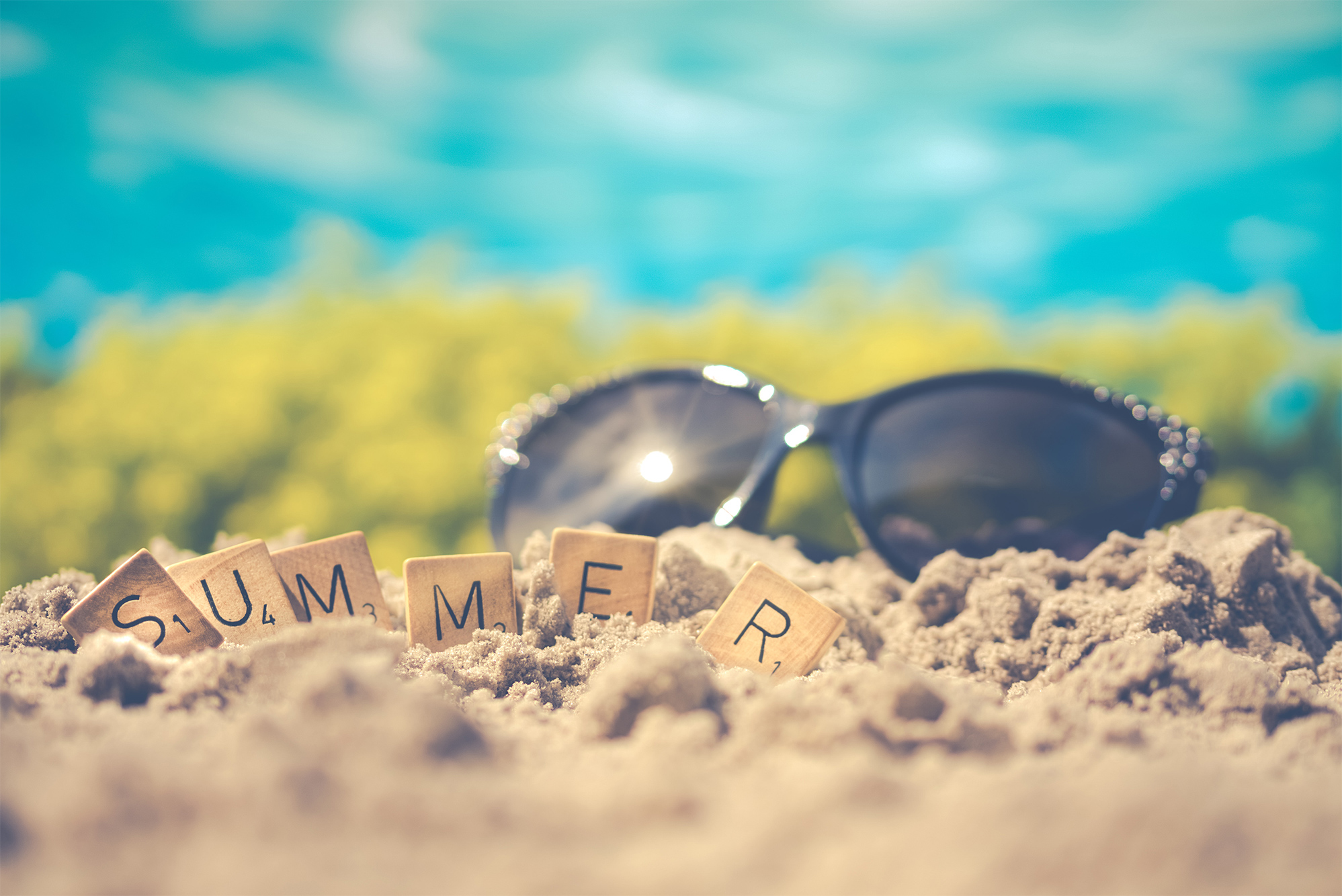 scrabble letters spelling out summer in the beach sand