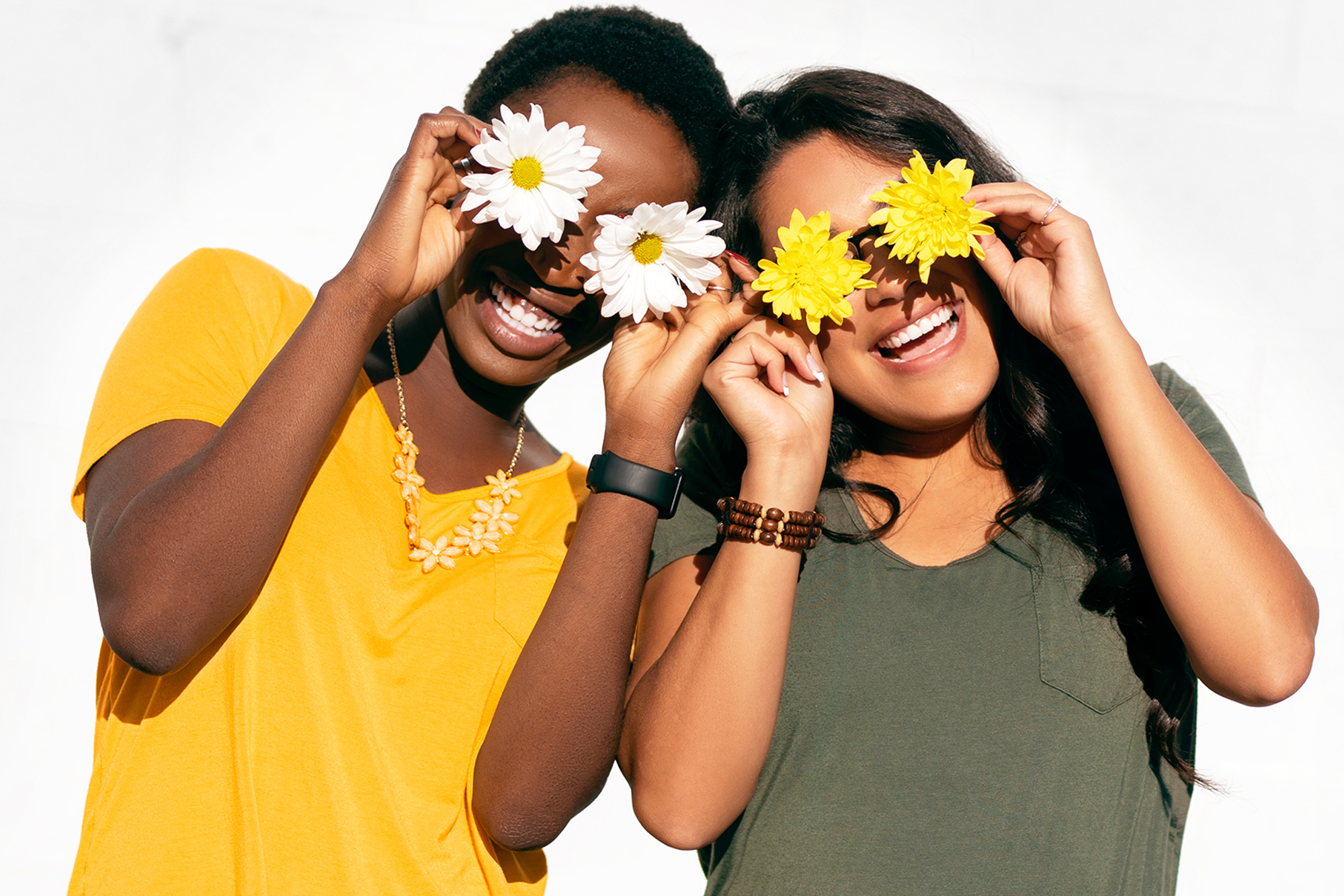 Girls holding flowers in front of their eyes while laughing