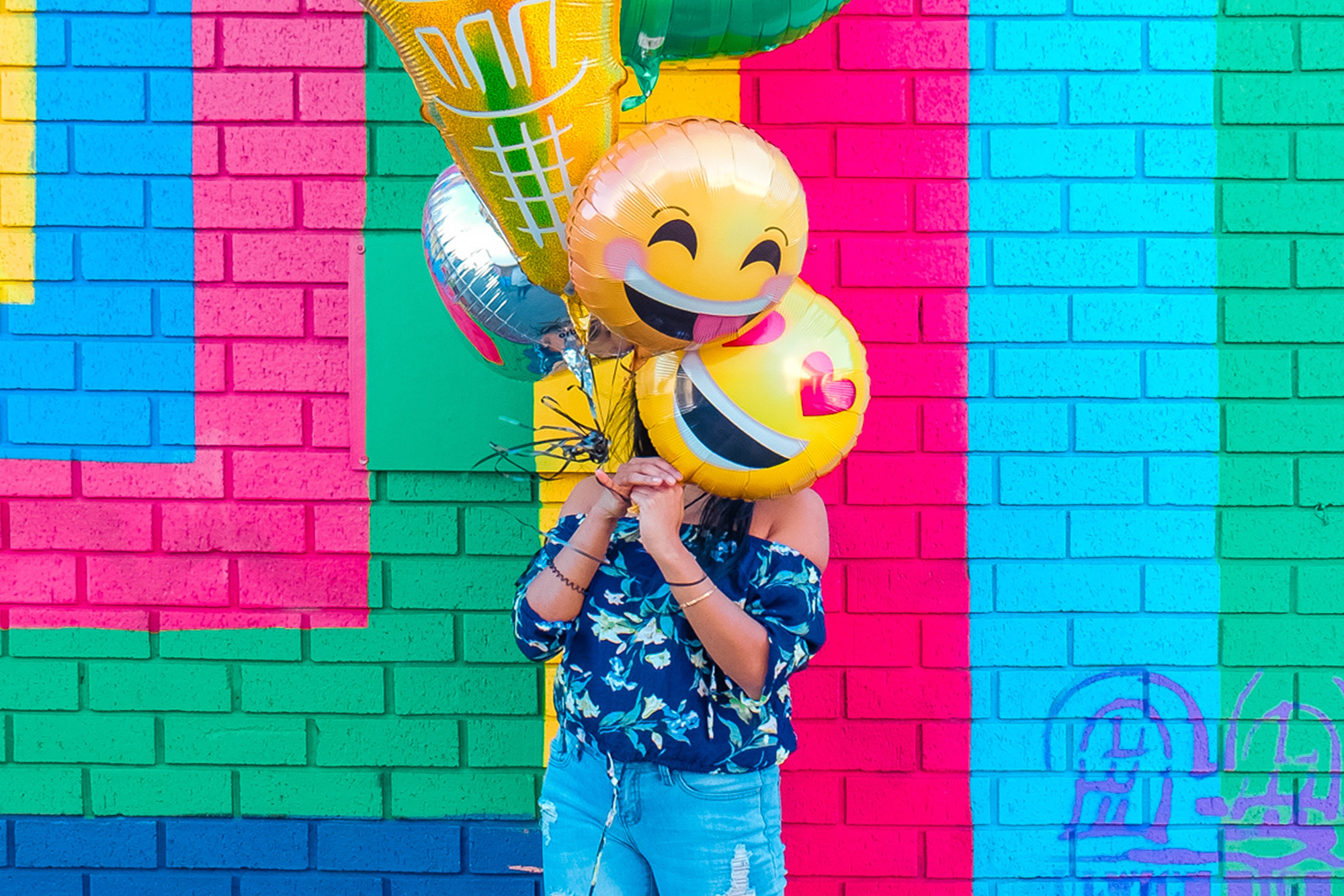 Woman holding emoji balloons in front of a colorful wall