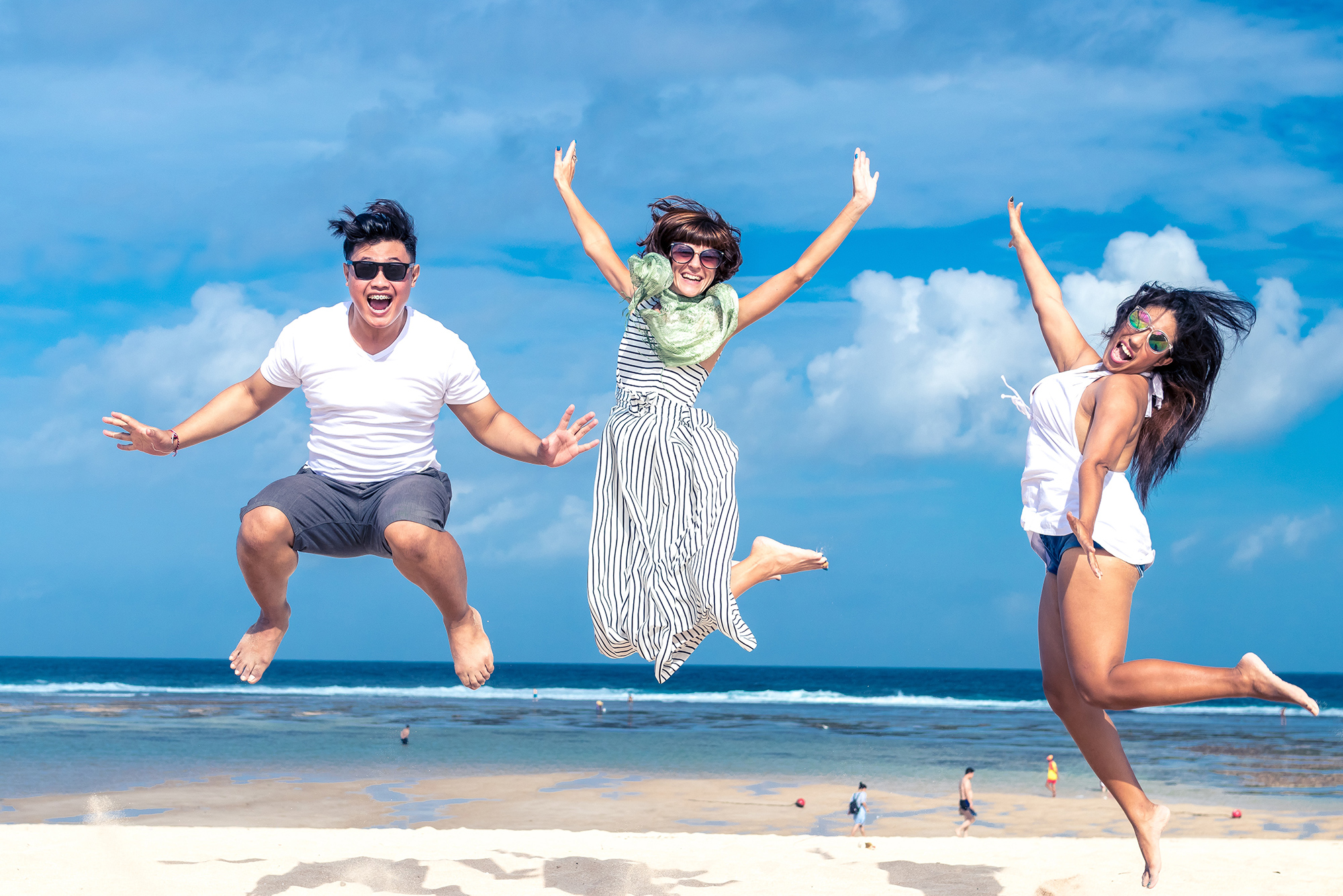 Group of friends jumping for joy on a beautiful beach