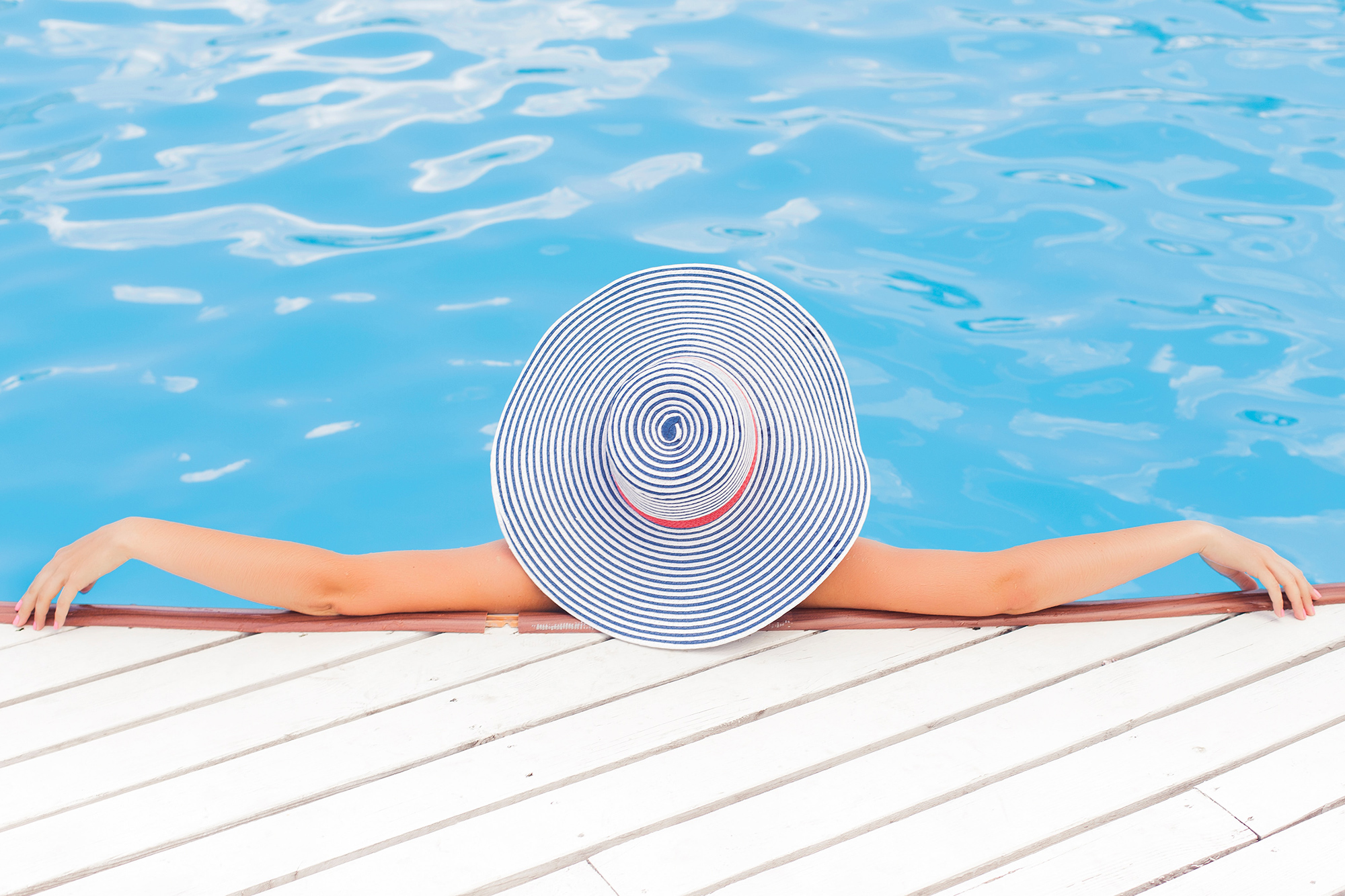 Woman with a hat relaxing in a pool