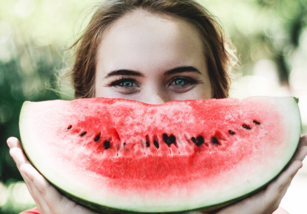 Woman holding a watermelon in front of her face as a smile