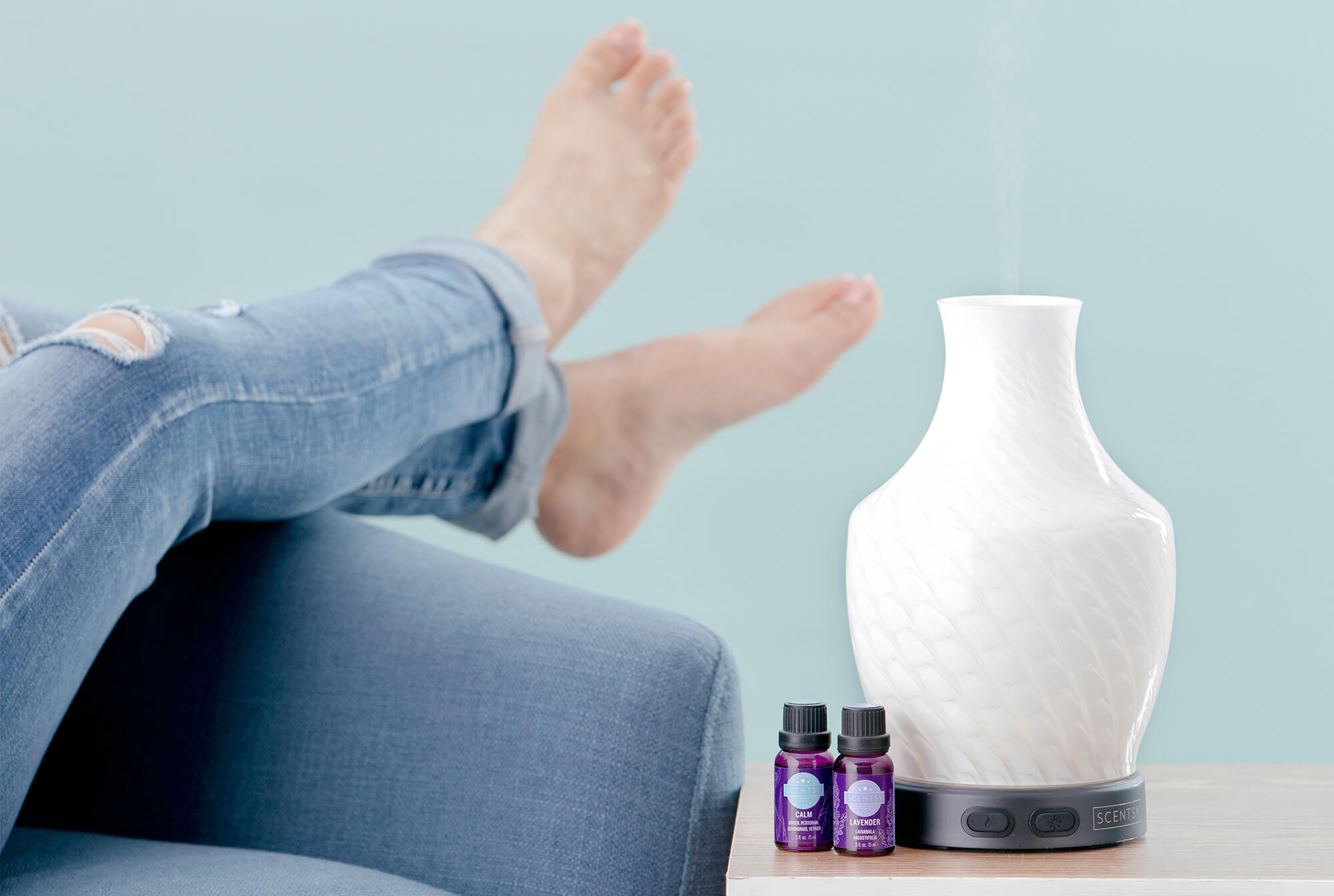 Woman relaxing on couch with her Scentsy diffuser warming Scentsy oils