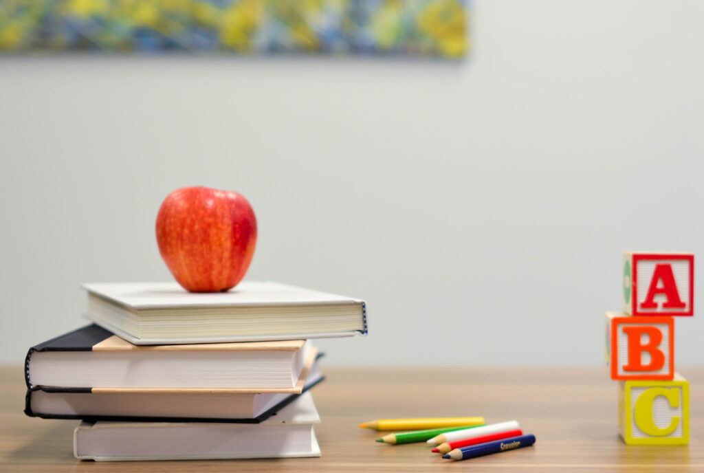 Apple on a stack of books with ABC blocks and pencils on a table