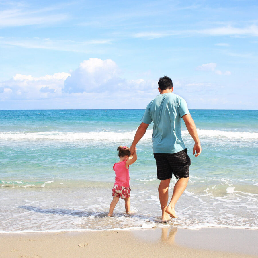 father walking on beach with toddler