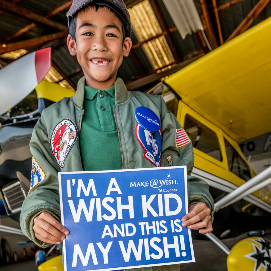 little boy holding a Make A Wish sign in front of plane