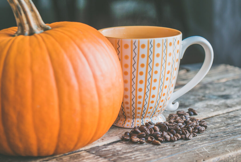 Pumpkin next to a coffee mug and coffee beans on the table
