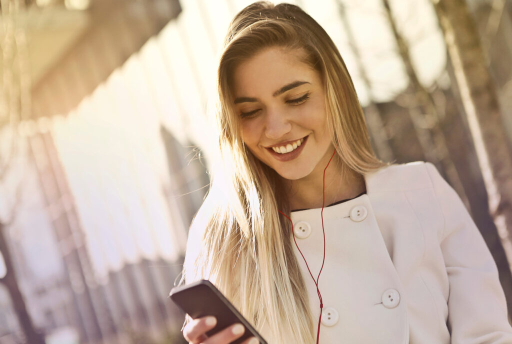 Woman smiling while listening to music through headphones