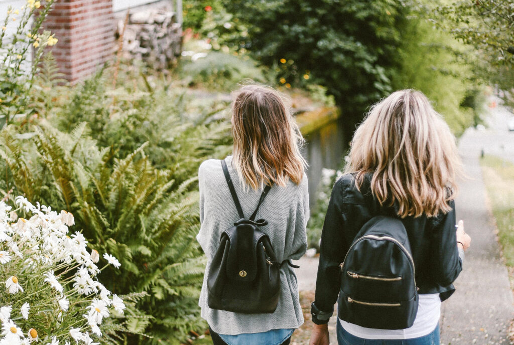 Two women walking down the sidewalk next to some bushes