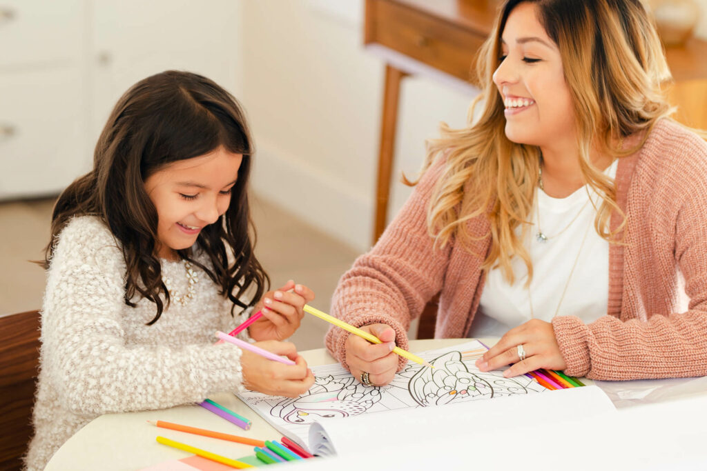 Mother and daughter drawing on table smiling
