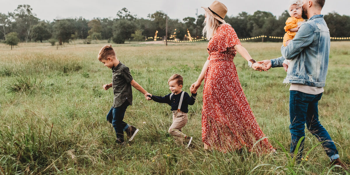 Family of five walking through a field with lights in the background