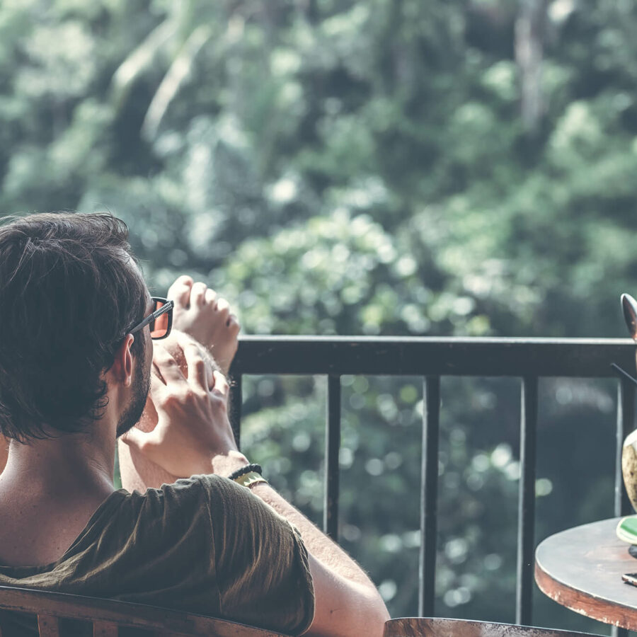 Man relaxing on porch with a coconut