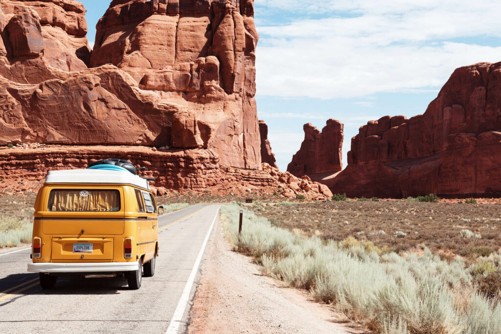 Yellow van driving on highway with giant rock structures and a brush field
