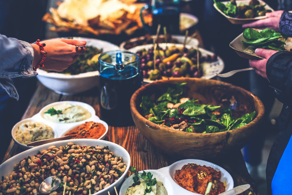 People gathered around a table with food for a potluck event