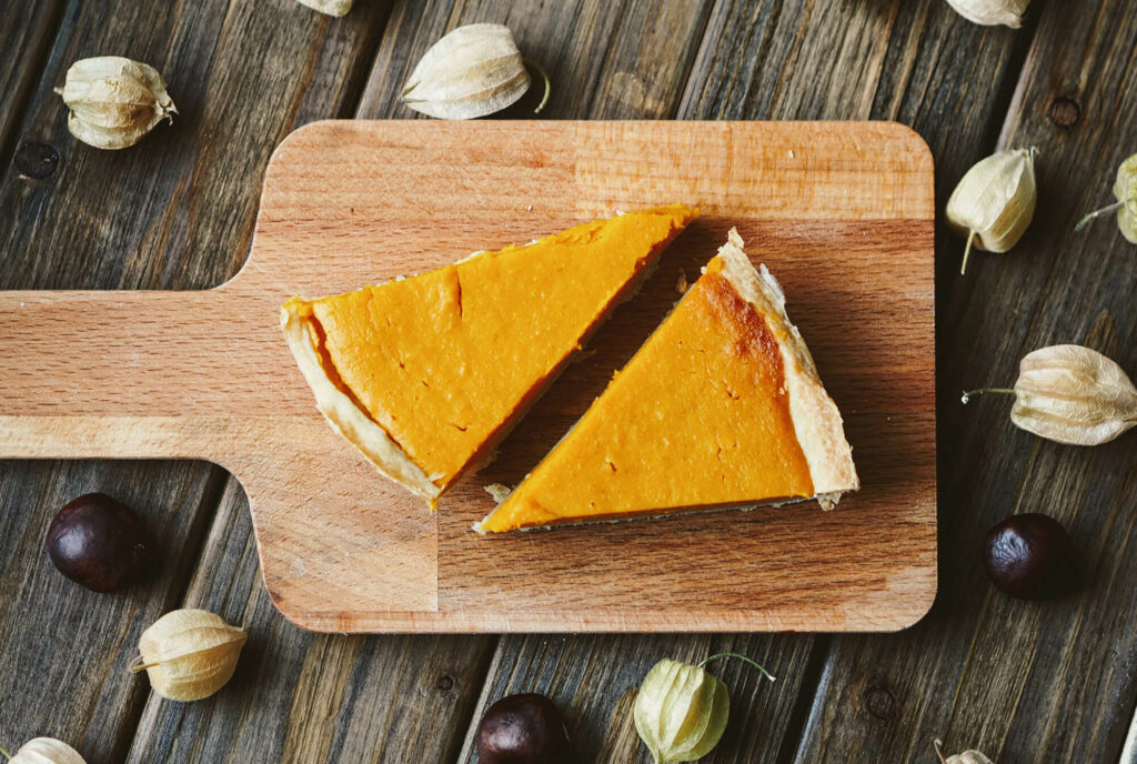 Two pumpkin pie slices on a wooden board