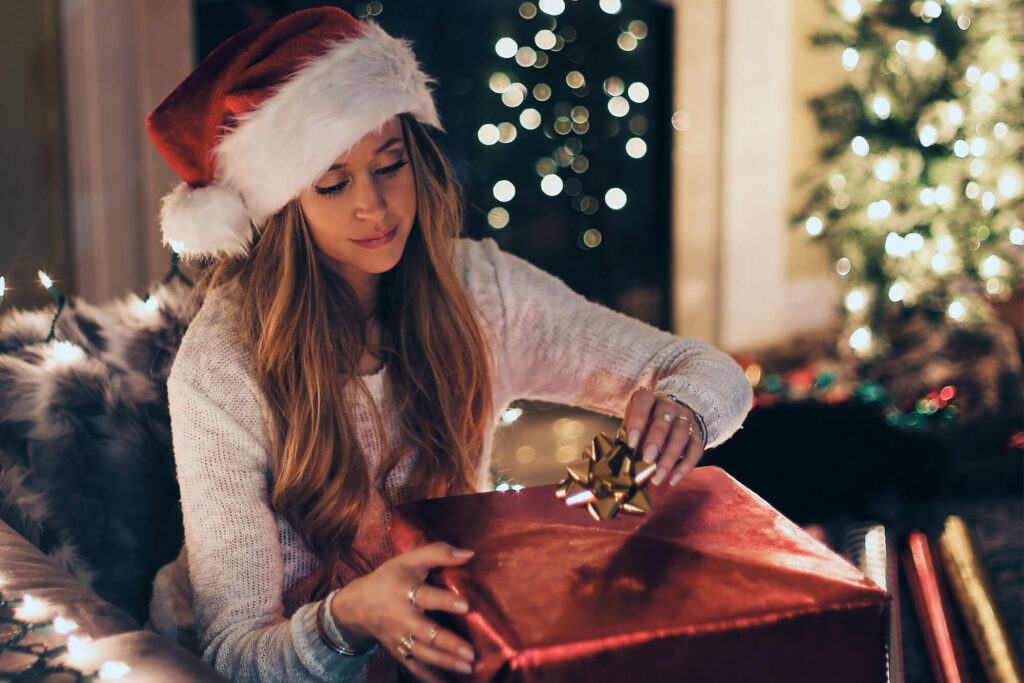 Woman wearing Santa Claus hat putting a bow on a wrapped present