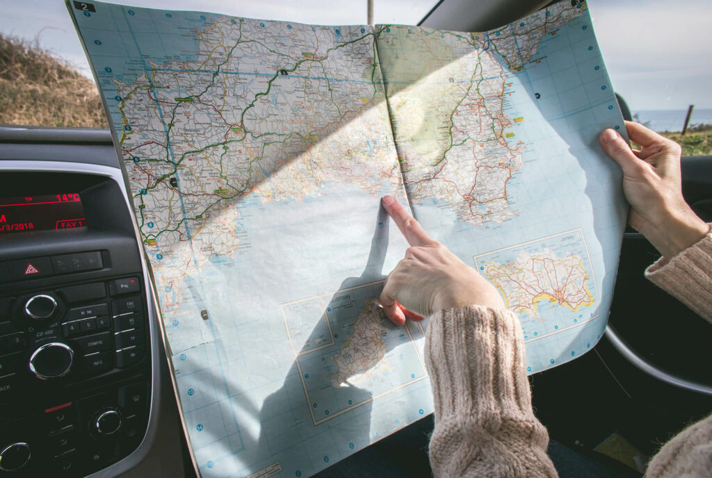 Person pointing out location on a map while in a car on a roadtrip