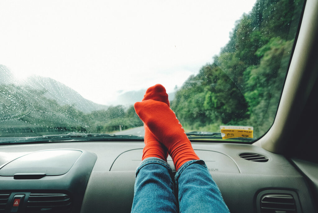 Person resting their feet on the dashboard of a car while on a roadtrip